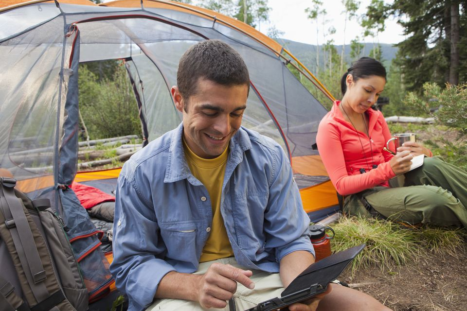 Man using digital tablet while camping