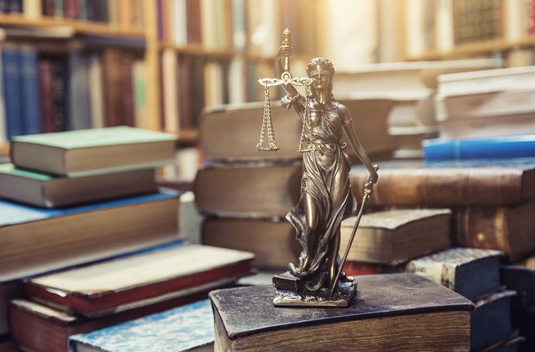 Lady Justice statue on law books