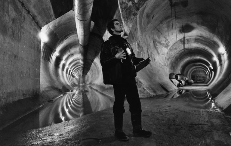 A man standing at a point where two tunnels connect in the Chunnel.