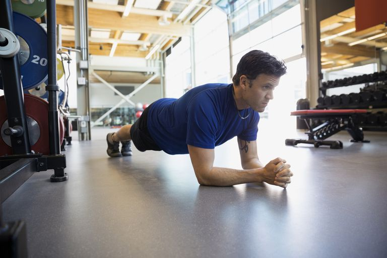 Man holding plank position at gym