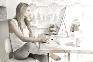 Woman using computer and drinking tea at home office