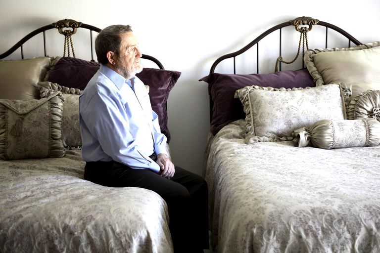 Senior man sitting on bed