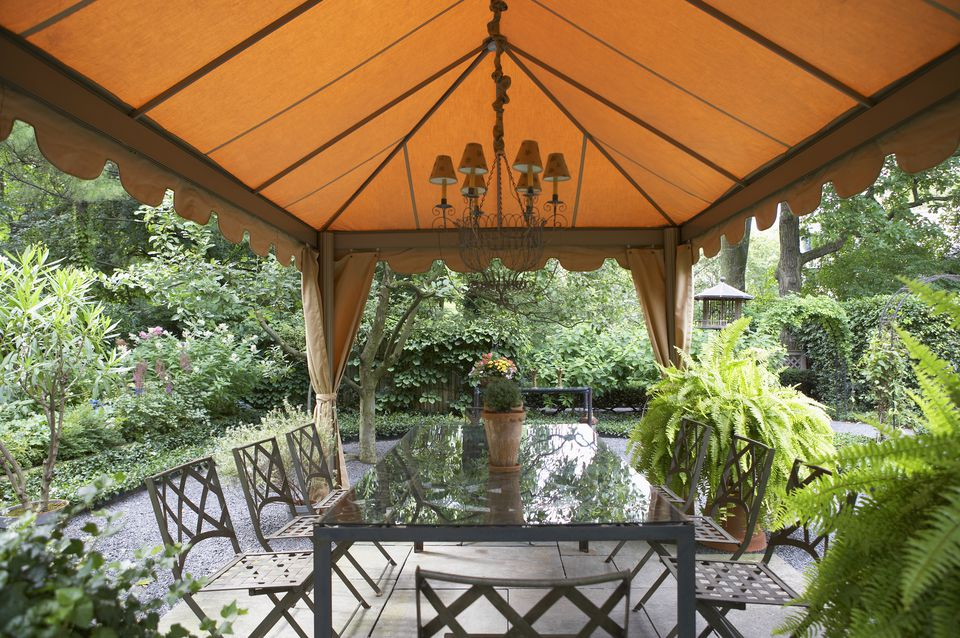 Fabric gazebo with chandelier and a rectangular dining table.