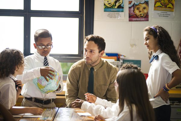 Teacher Helping Group of Students with a Project