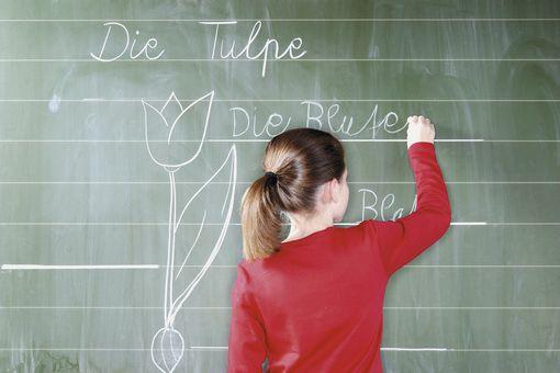 Student writing on chalkboard.