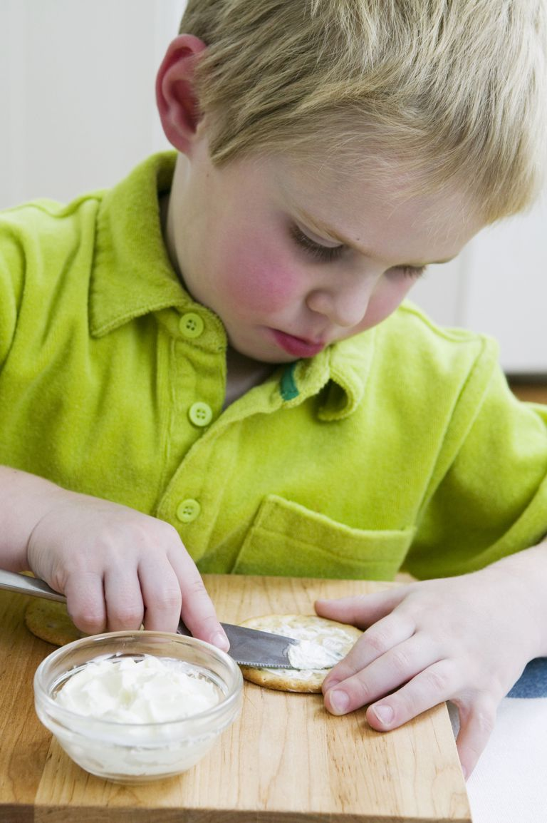 Boy using knife to spread cream cheese on savoury biscuit