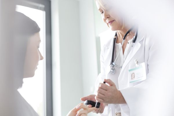 Doctor testing patient blood sugar for diabetes in examination room