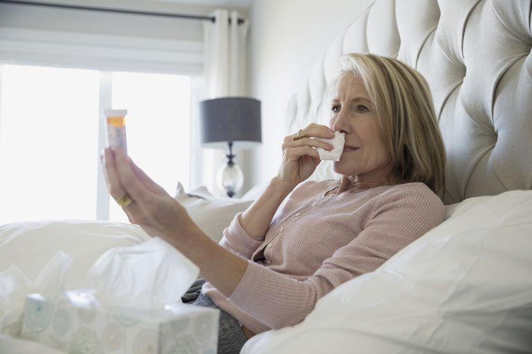 Sick woman in bed holding pill bottle