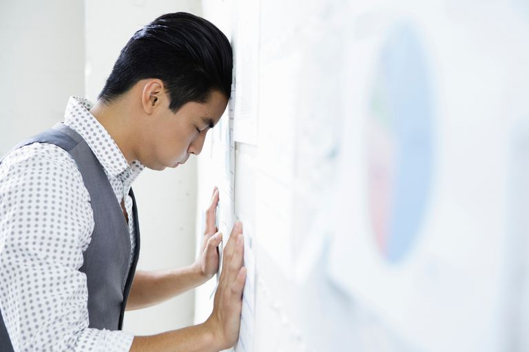 Young man in office with head and hands against wall