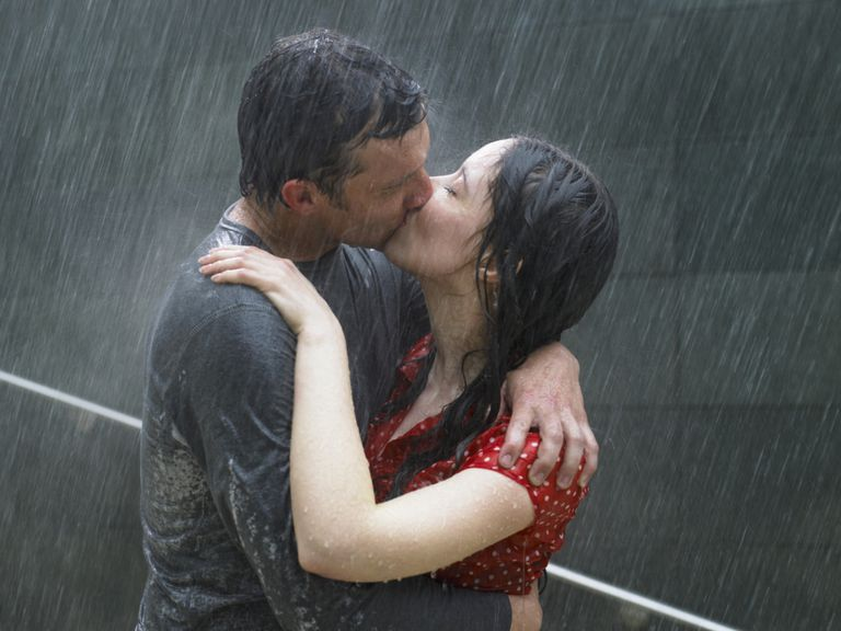 Man and woman kissing in the rain.