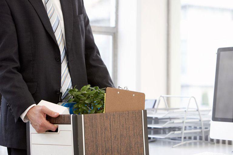 businessman carrying file box of belongings