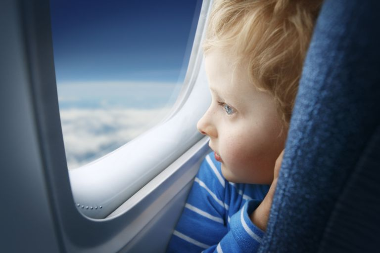 Boy watching sky through the airplane window