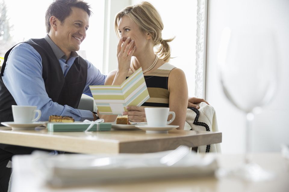 Man surprising woman with card at bistro table