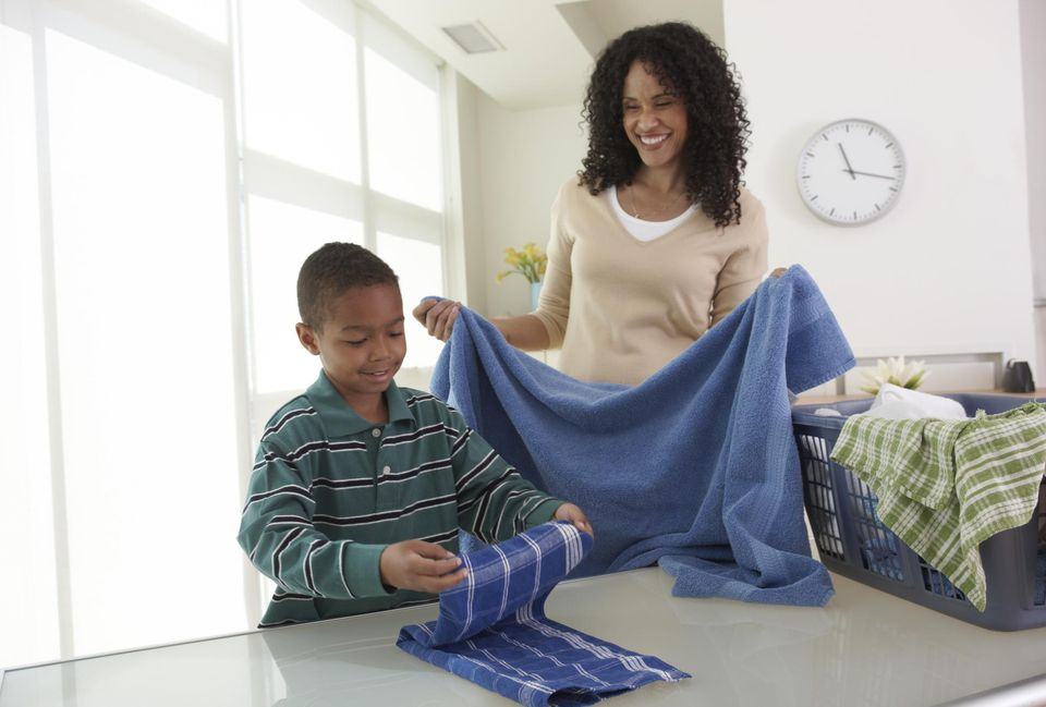 Black mother and son folding laundry together