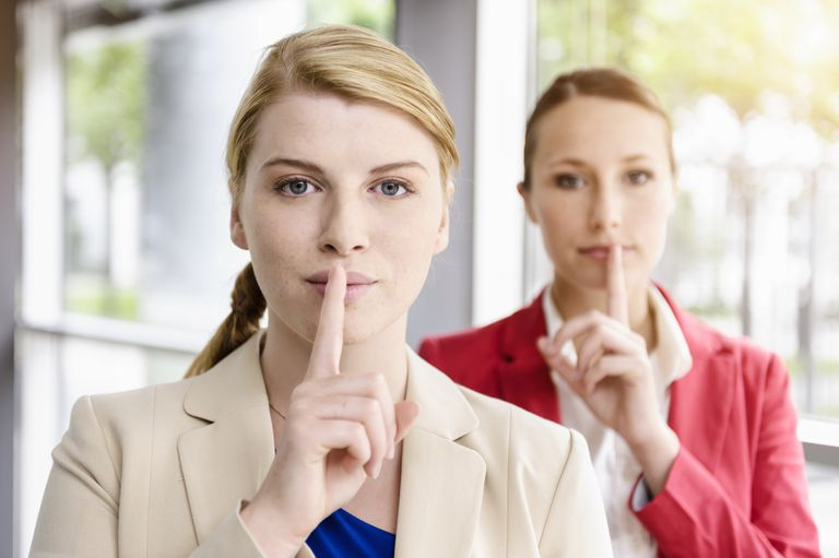 Two women making the silence finger motion