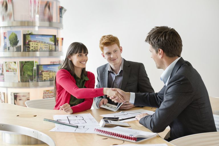 Young couple shaking hands with bank manager