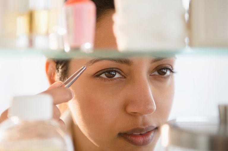 Close up of Asian woman tweezing eyebrows