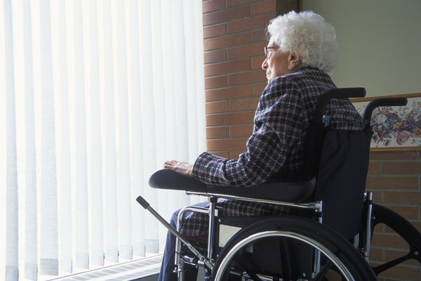 Senior woman on wheelchair looking out of window with blinds