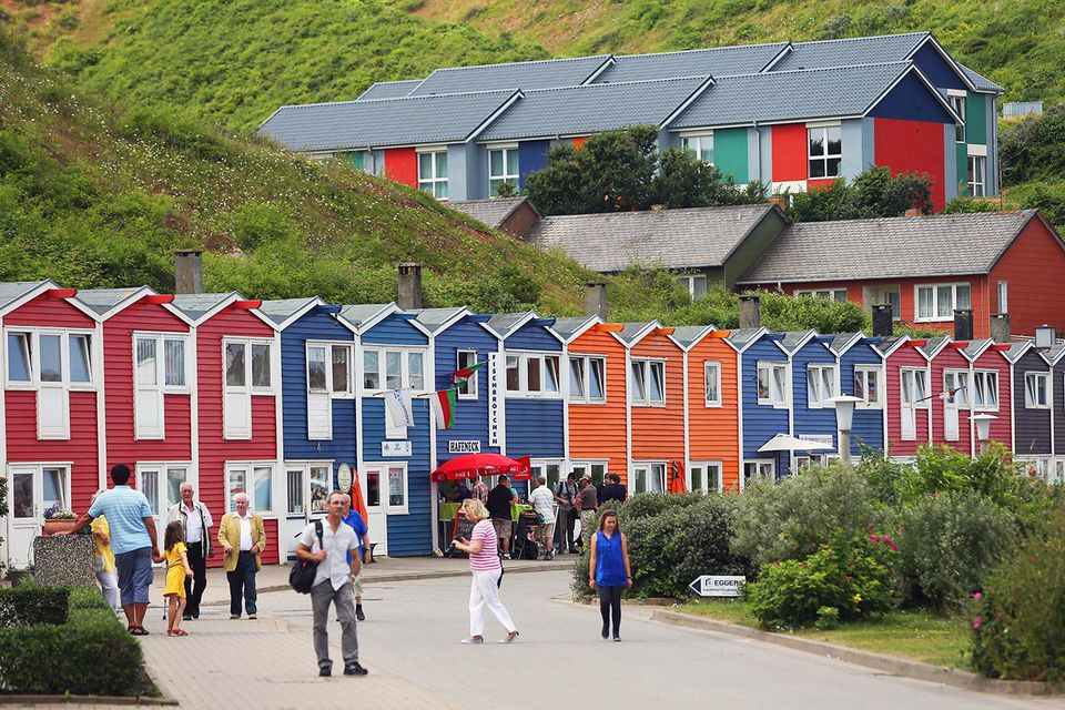 Summer tourists walk among houses built after World War II in Helgoland town on August 3, 2013 on Heligoland Island, Germany.