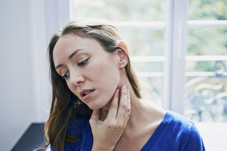 Woman suffering from sore throat. France