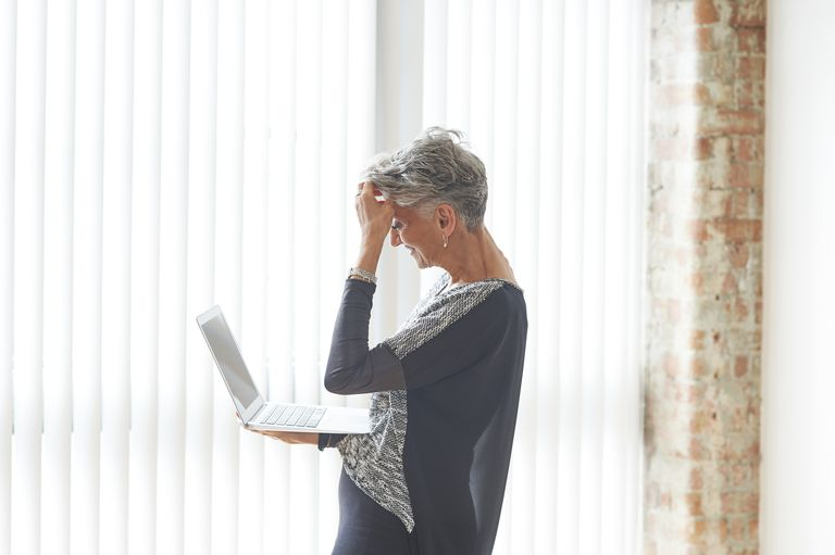 Stressed older woman using laptop