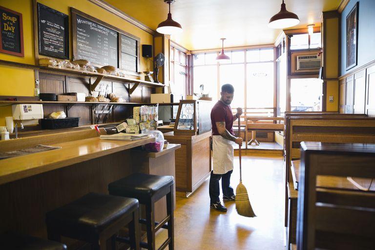 Man sweeping floor inside a restaurant