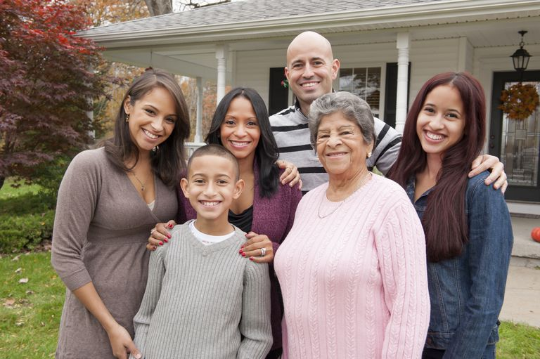 Portrait of a family smiling in front of home