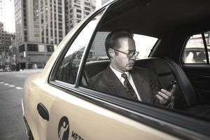 Man Checking Cell Phone in Cab