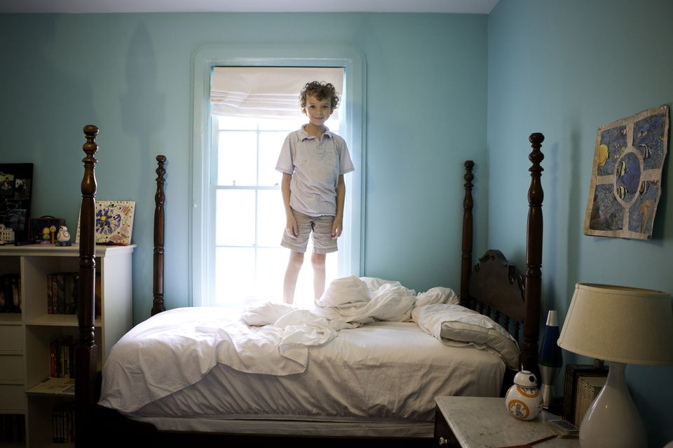 Young boy standing on unmade 4 poster bed backlit