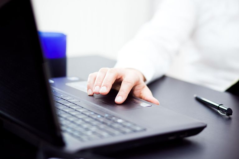 Woman's hand working with laptop in office