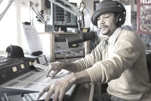 Mixed race disc jockey using control panel in studio