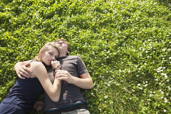 Teenagers cuddling in the grass