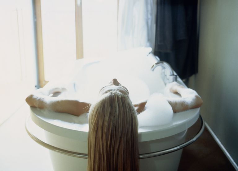Young woman lying in a bath