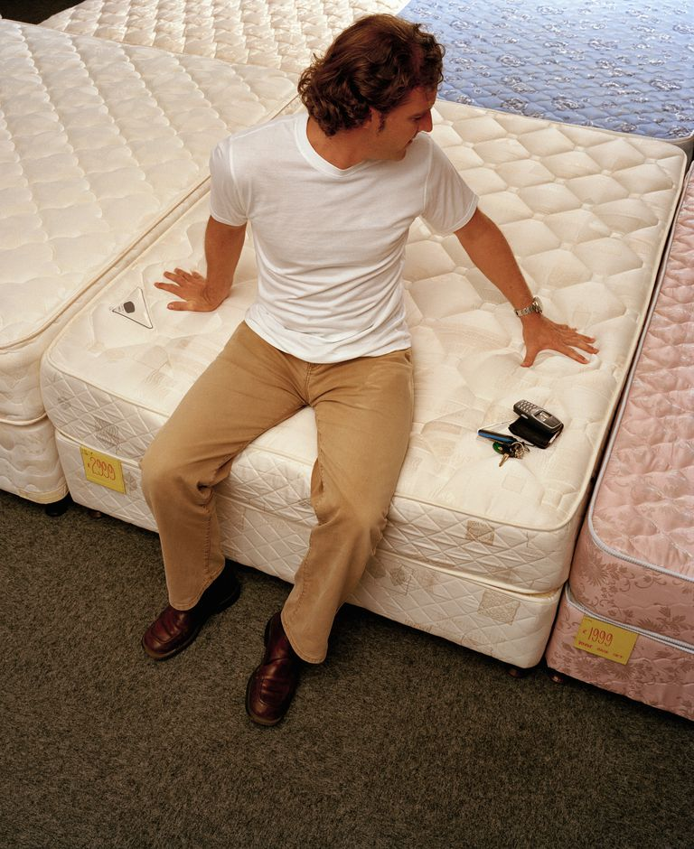 Man sitting on mattress in furniture shop, elevated view