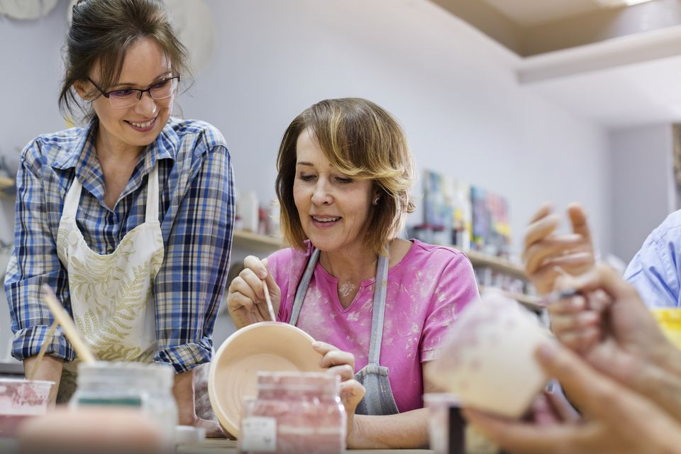 Mature woman painting pottery in studio