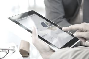 Business people reviewing data on digital tablet