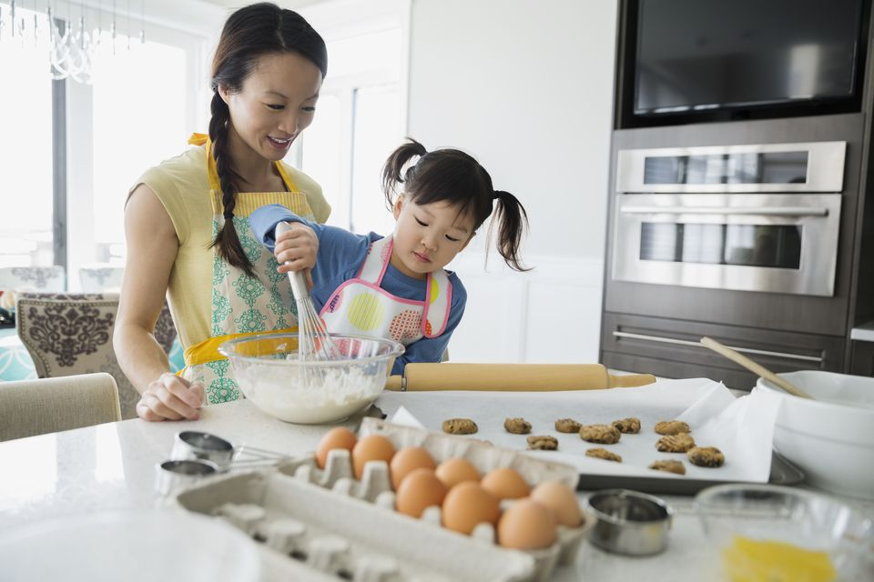 Mother and daughter baking cookies in kitchen