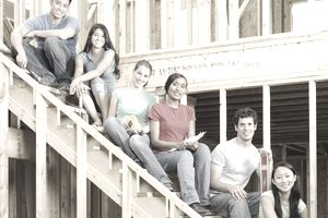 Young volunteers on stairs of home at community service project, portrait