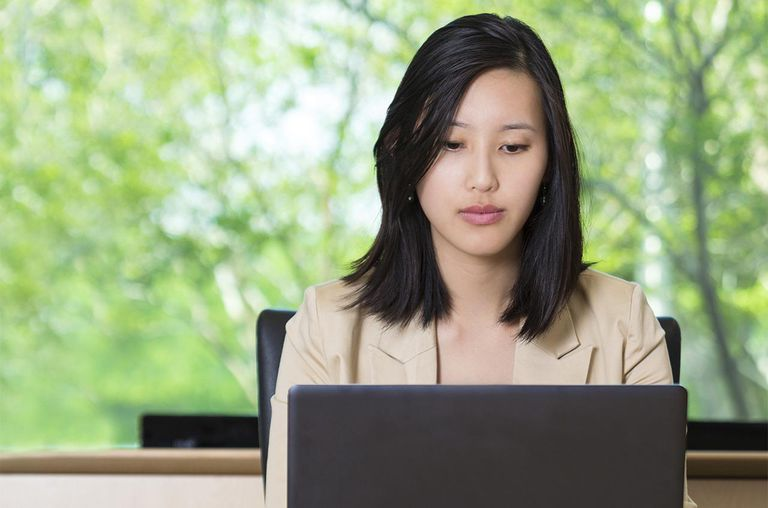 Young Asian businesswoman working on laptop in board room