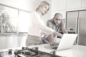 couple looking discouraged at laptop in kitchen