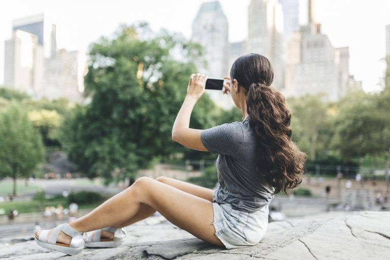 young woman with teased ponytail taking photo with phone