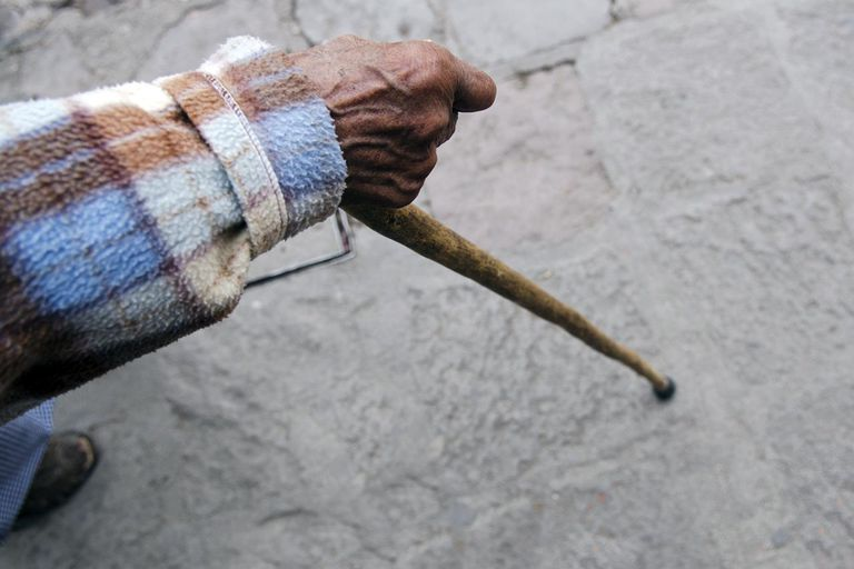 Old woman's hand holding cane on sidewalk