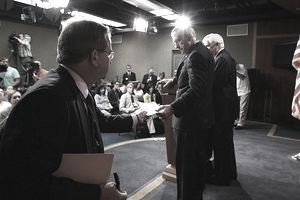 Senate Majority Leader Harry Reid (D-NV)(C), is handed a note while he and Senate Banking Committee Chairman Christopher Dodd (D-CT)(R), speak to the media after the final vote on Wall Street reform, July 15, 2010 in Washington, DC.