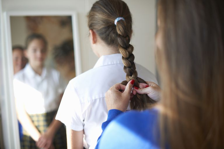 mother braiding teen girl's hair