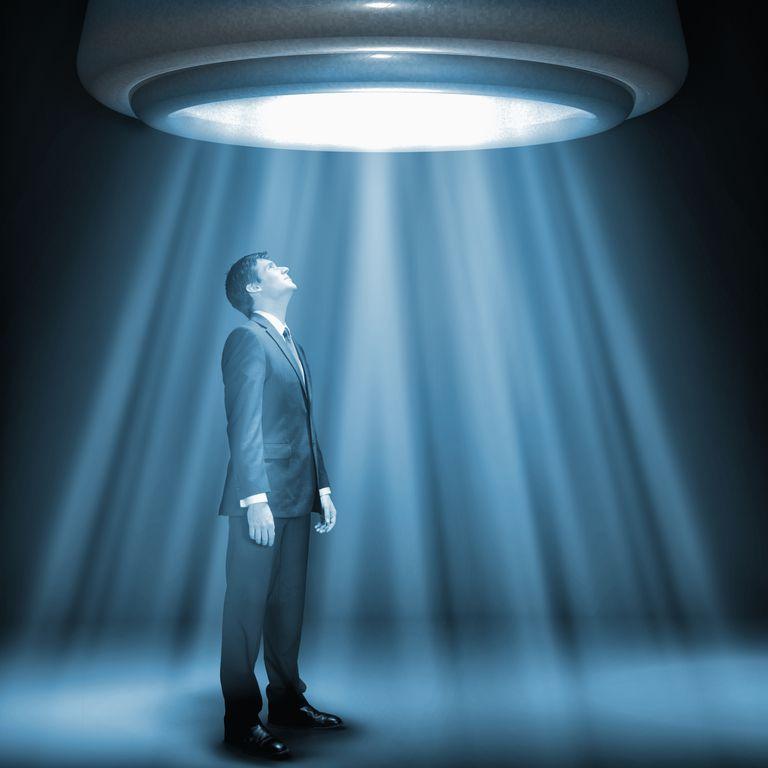 Caucasian businessman standing underneath glowing lights