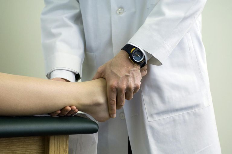 Doctor examining patient's feet and ankle