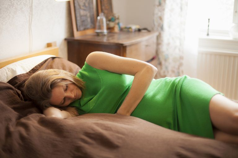 Pregnant woman wearing green dress resting in bed
