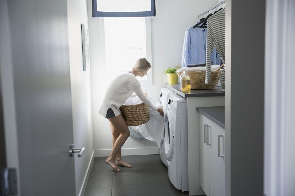 Женщина, удаление листов из сушилки в прачечной