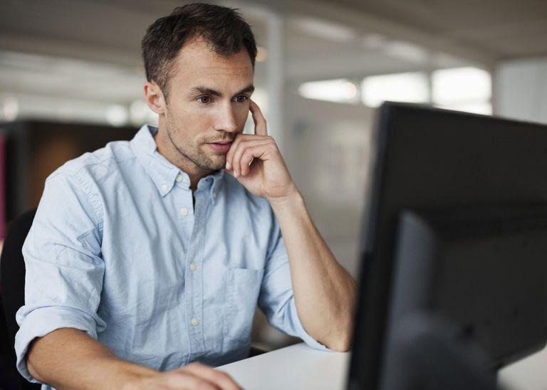 Businessman using desktop PC at desk in office