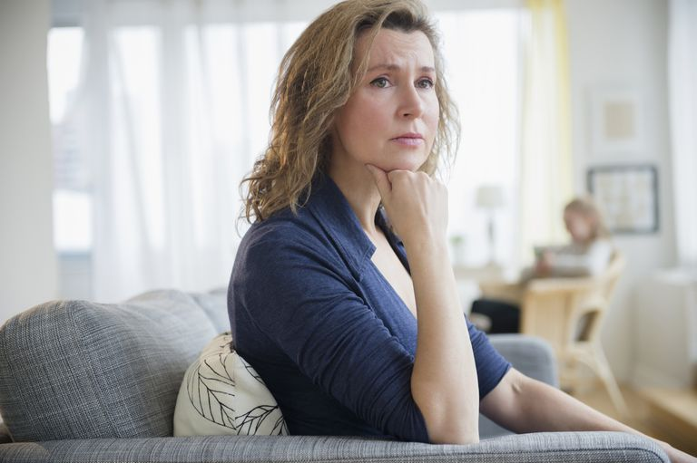 concerned woman sitting on couch